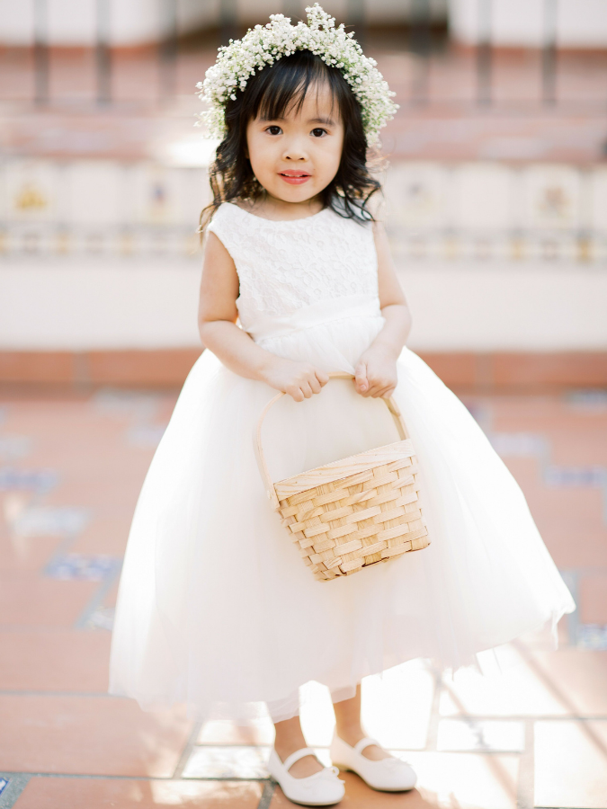 Flower girl in white dress with basket and flower crown