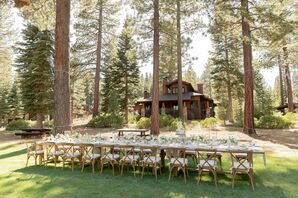 Reception Tables and Wood Cross-Back Chairs Under Towering Trees at Martis Camp in Truckee, California