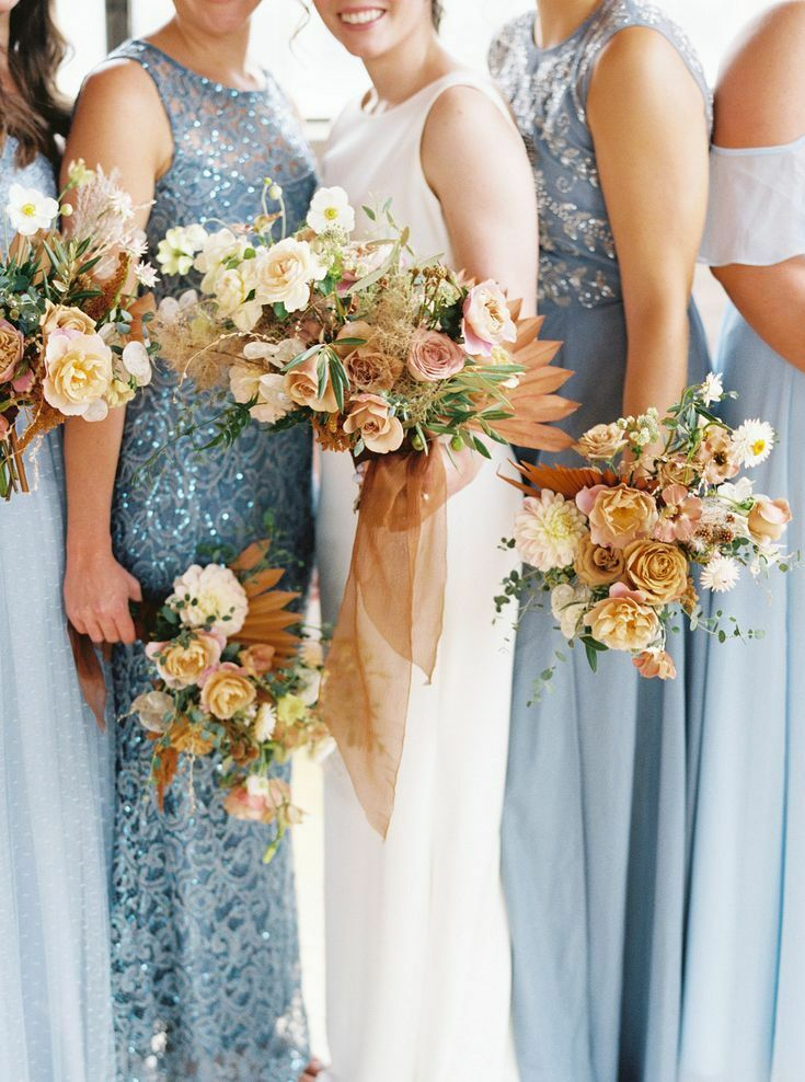 Bridesmaids in blue dresses holding yellow bouquets