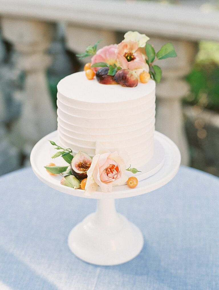 Simple one-tier wedding cake with fresh fruit and flowers atop white cake stand