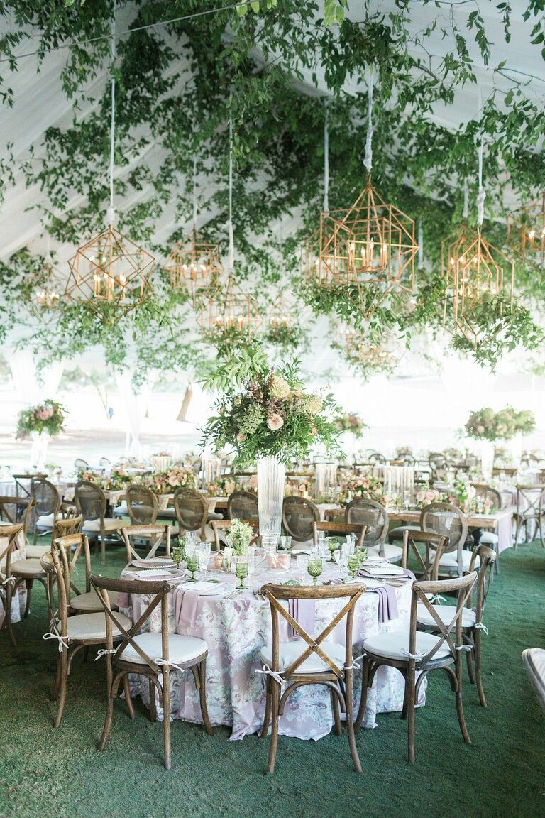 Romantic garden-inspired tented reception with gold chandeliers and cross-back chairs