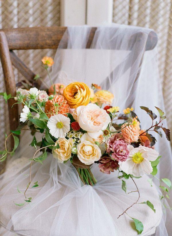 Orange wedding bouquet sitting on chair with veil