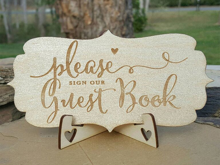 Wooden engraved sign with 'please sign our guest book' in cursive