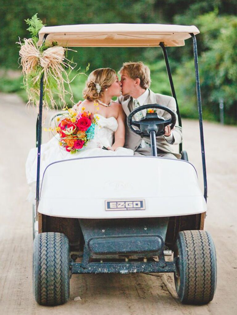 Bride and groom entering wedding on golf cart
