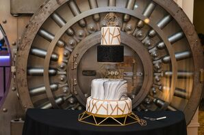 Modern Black-and-Gold Wedding Cake in Front of Historic Bank Vault