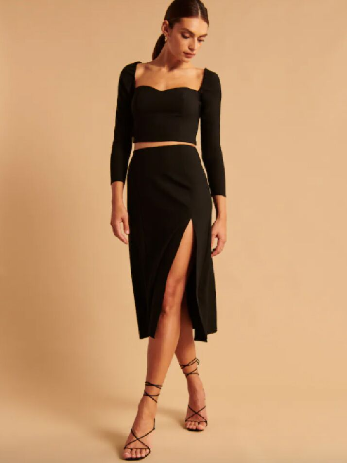 Black long sleeve crop top with portrait neckline and matching black midi skirt