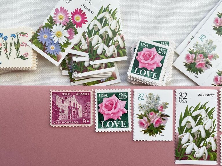 Four styles of vintage stamps featuring flowers and the Alamo on pink envelope