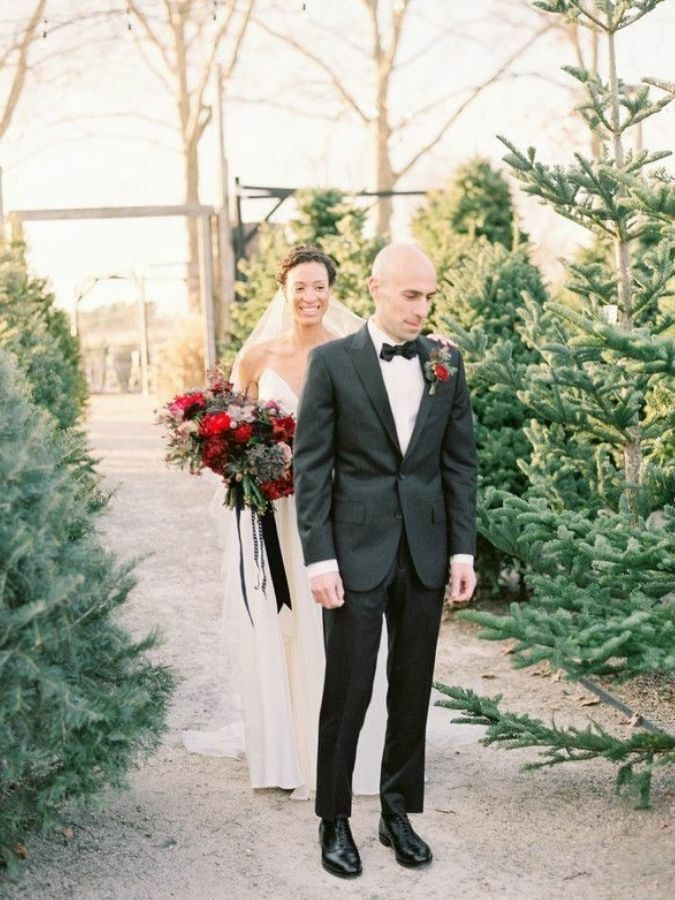 Couple during first look surrounded by Christmas trees