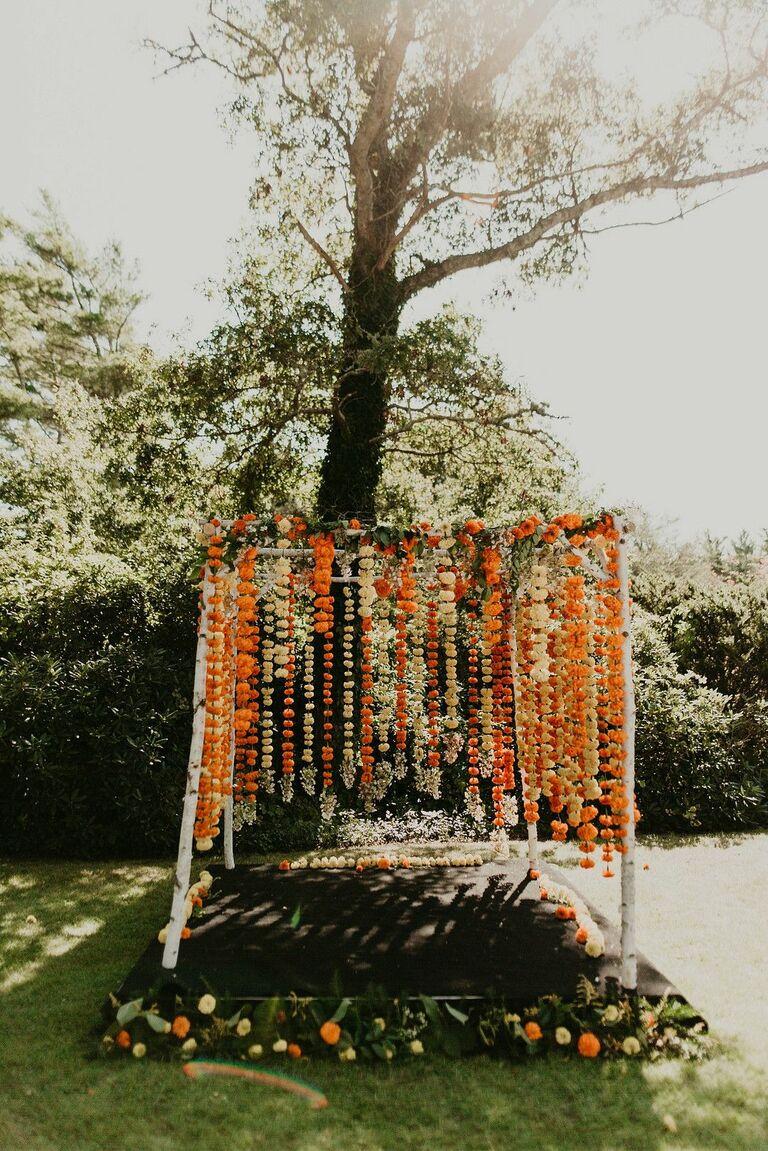 Rustic mandap with orange flower garlands