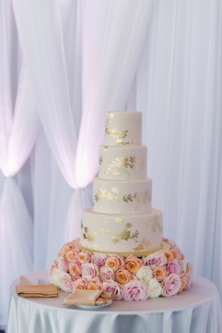 Gold-and-white wedding cake with fresh rose cake stand