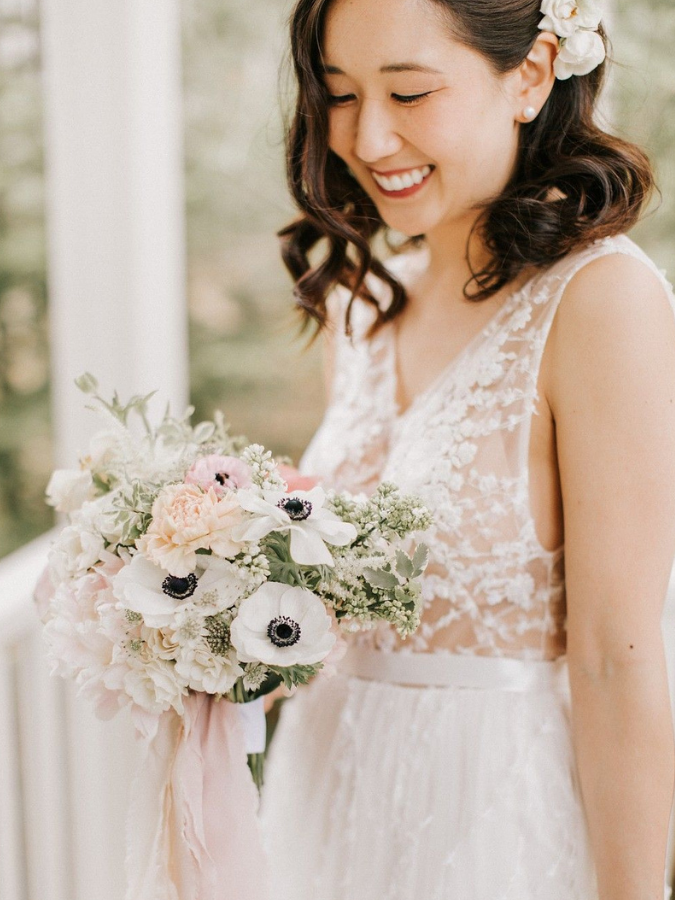 Bride holding anemone bouquet and smiling