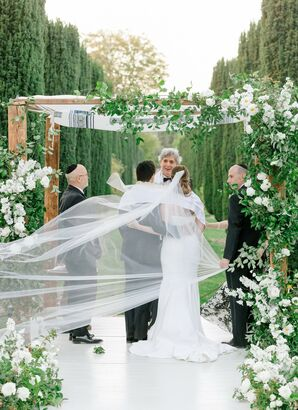 Couple Standing Under Greenery-Covered Chuppah With Veil Flowing in the Wind