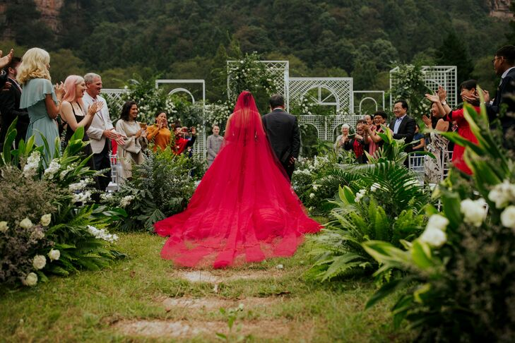 Bride Processing Down Ceremony Aisle Wearing Red Veil