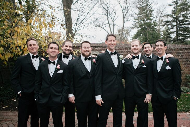 David and his groomsmen wore classic black tuxedos and bow ties from Black by Vera Wang. David wore a white rose boutonniere to distinguish himself from his groomsmen, who wore pink rose boutonnieres.