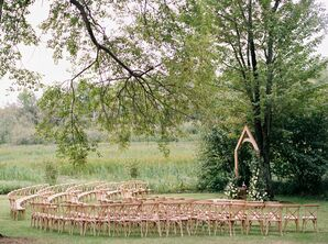 Forest Wedding Ceremony With Cross-Back Chairs and Wood Arch