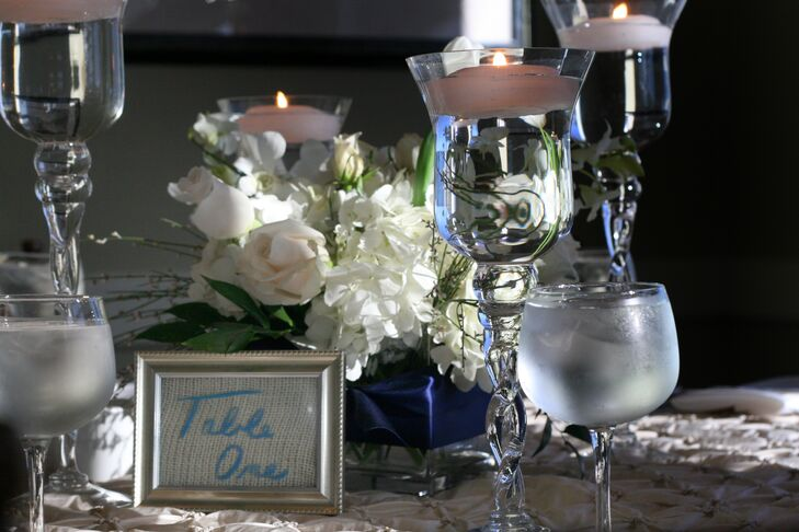 Centerpieces at the reception were made up of white roses and hydrangeas with floating candles in silver candleholders. Table numbers were displayed in silver frames that matched the centerpieces.