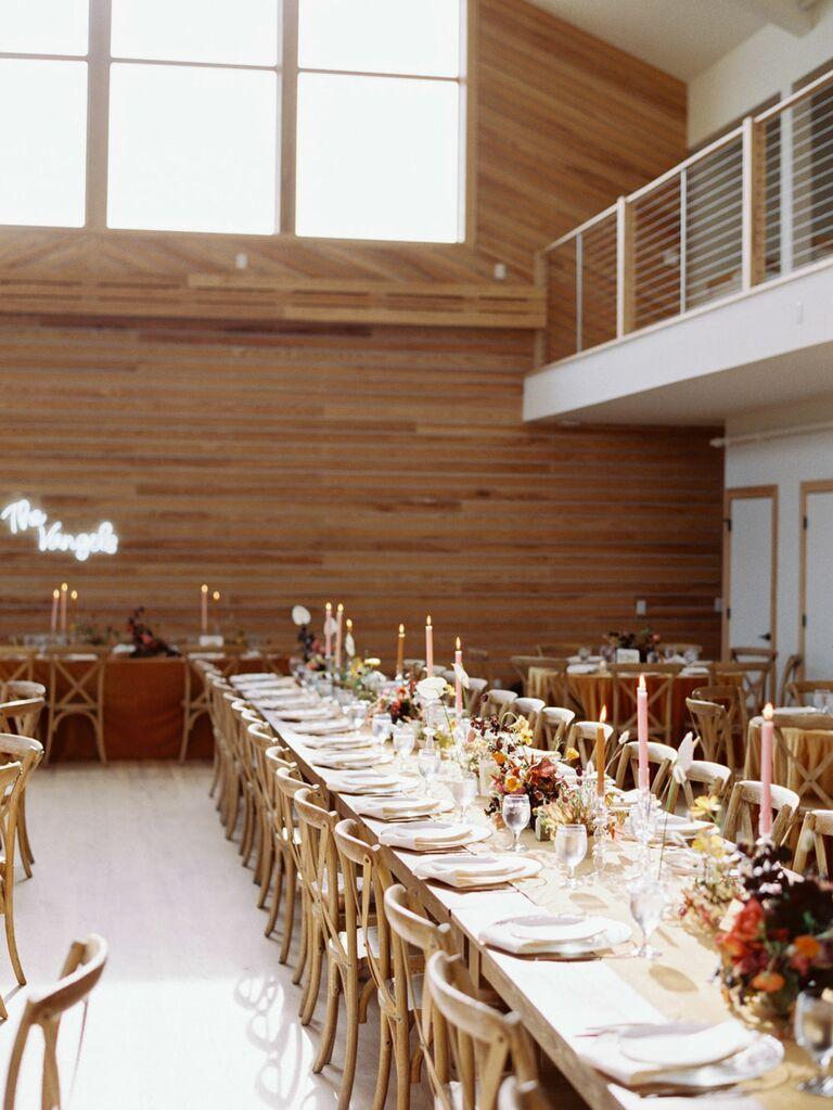 Barn wedding reception venue with retro boho centerpieces and custom neon sign