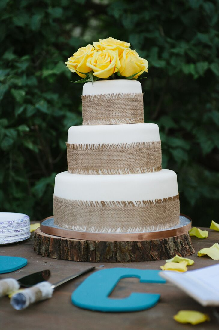 The three round tiers of the wedding cake were wrapped in burlap and topped with fresh yellow roses to complement the rustic farm aesthetic.