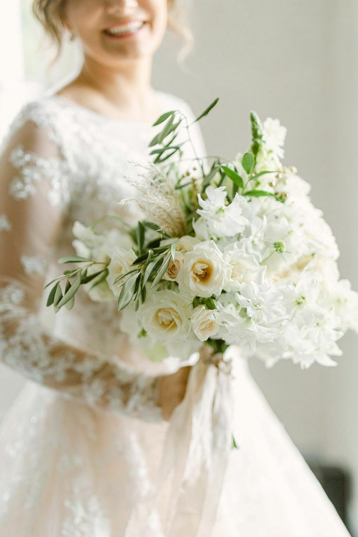 Bride holding white-and-green bouquet