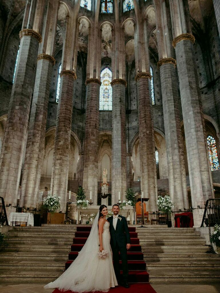 Bride and groom posing in gothic cathedral at dark academia wedding