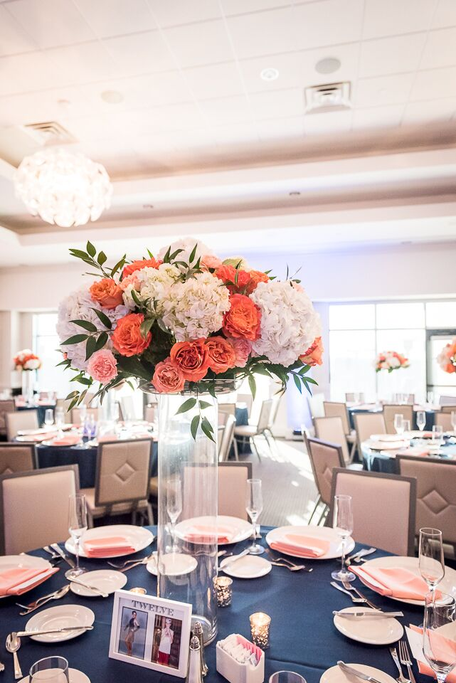 """Julia's love for """"fluffy flowers"""" came out in the centerpieces. White hydrangeas, coral garden roses and pink garden roses were placed on tall cylinder vases in what looked like and overflowing pomander. This """"fluff"""" could not be contained. It was that awesome."""