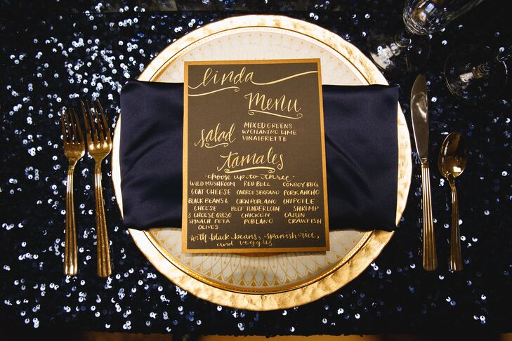 The menu cards doubled as escort cards, with each person's name added to the top of the menu card. Gold chargers provided the base for navy satin lamour napkins and gothic gold china.