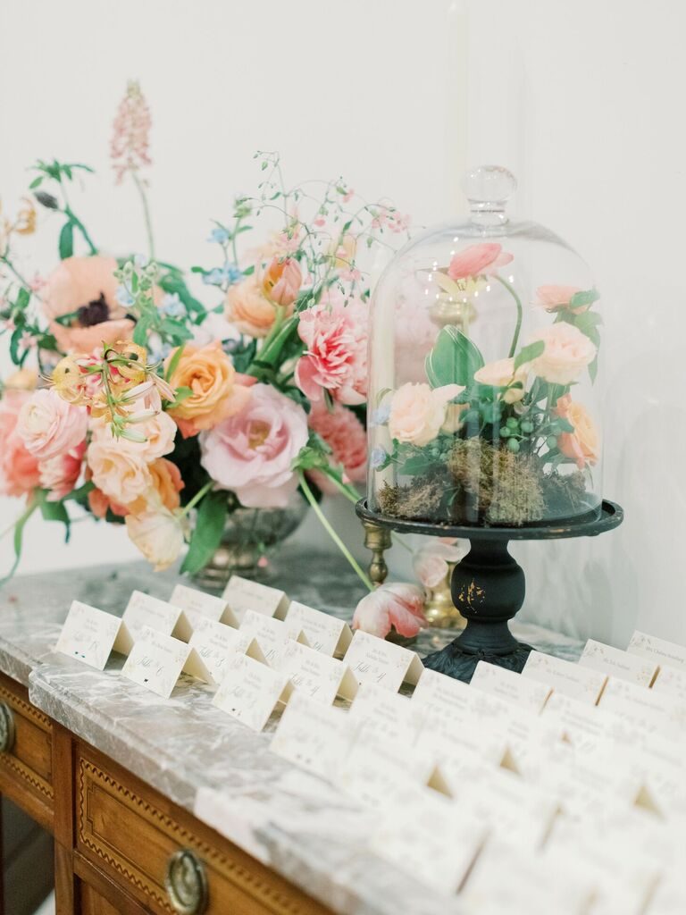 Escort card display with cloche-covered floral arrangement