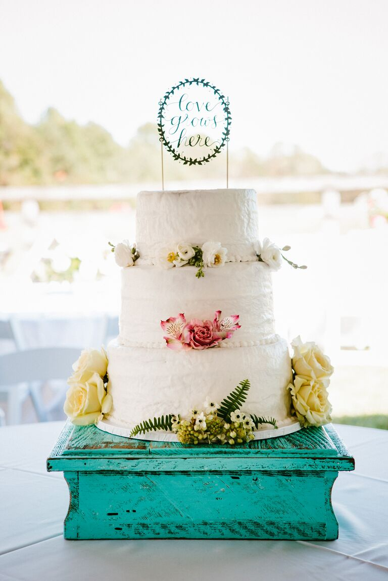 White textured buttercream wedding cake with garden topper