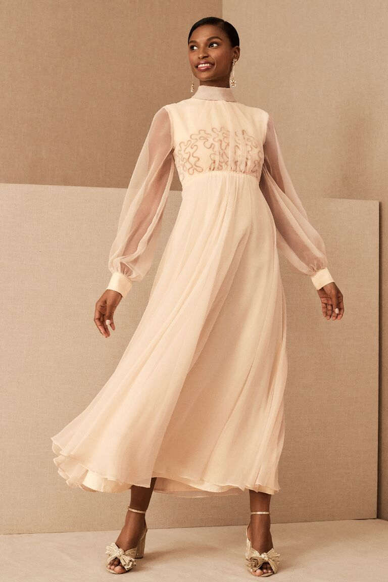 Vintage wedding dress with sheer cuffed long sleeves and swirly sequin pattern on bodice