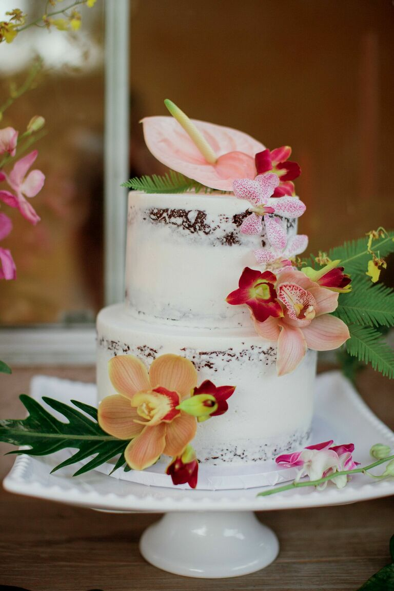 Semi-naked two-tier cake with tropical flower decorations