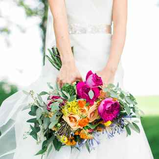 Brie holding bouquet with yellow, peach and magenta flowers