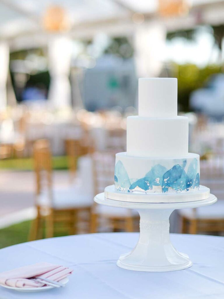 White tiered wedding cake with blue watercolor design