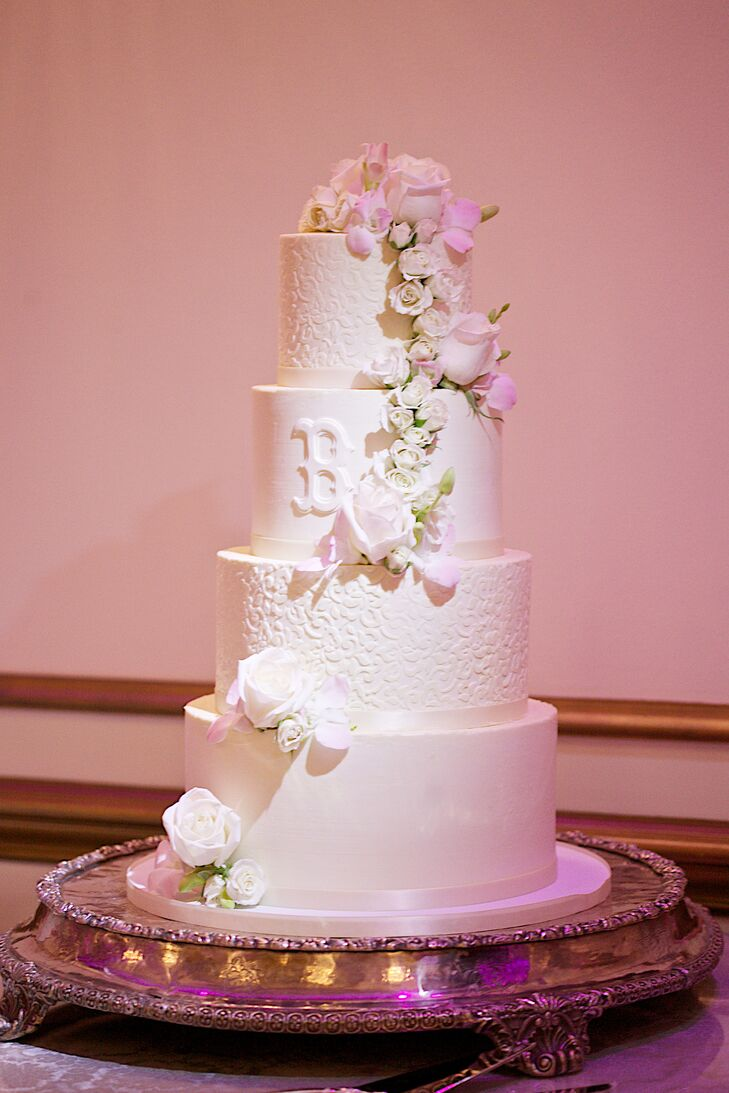 """Jessica and Billy enjoyed a four-tier round buttercream wedding cake decorated with an ornate floral lace pattern on every other tier. """"On the middle tier, we had the Boston Red Sox B,"""" Jessica says. """"Billy's family is originally from New England, and they are huge Red Sox fans. We thought it was befitting for his side of the family, and because our last name is Boska! I am not sure the New Jersey crowd were too thrilled about seeing that B though."""""""