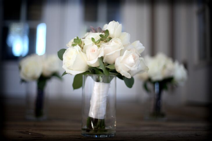 Melissa and her bridesmaids carried matching white rose and succulent bouquets wrapped in white ribbon.