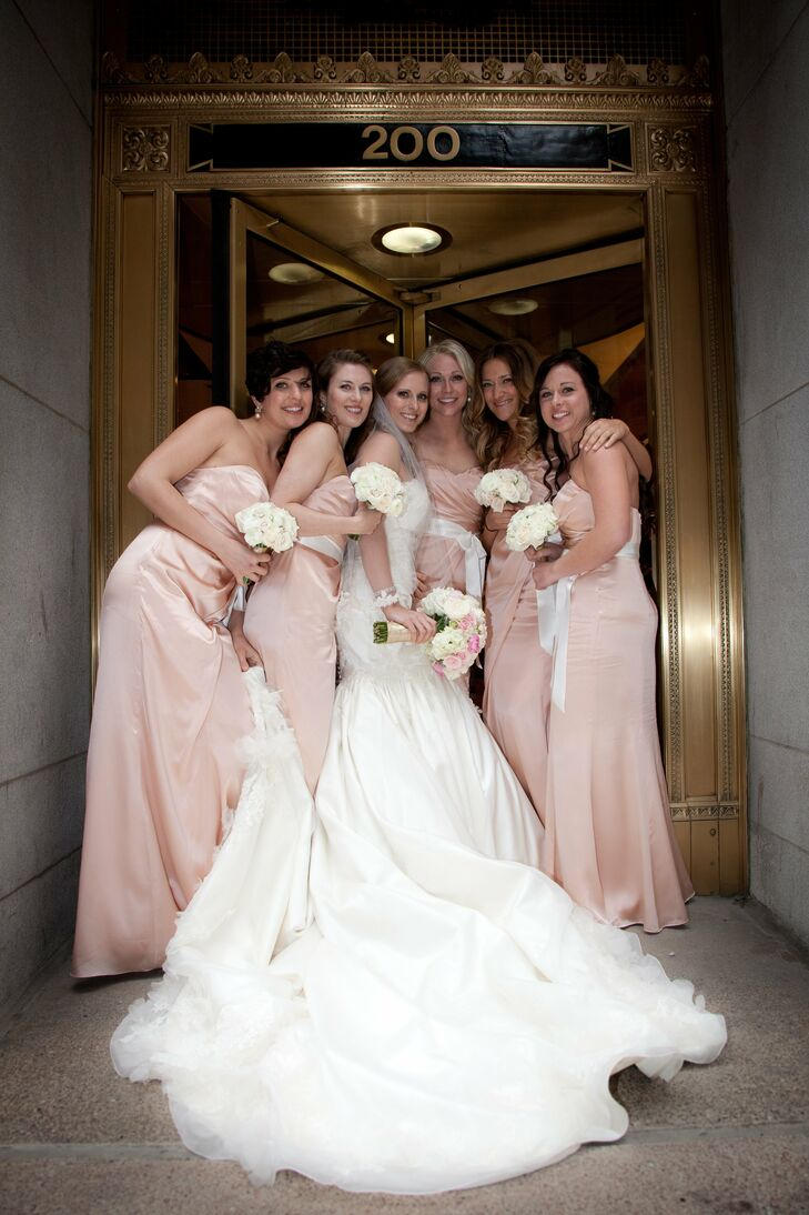 Kelly's nine-foot train was manned by five bridesmaids dressed in silk charmeuse blush gowns. Silk ivory satin ribbons were tied at the waist of each bridesmaid.