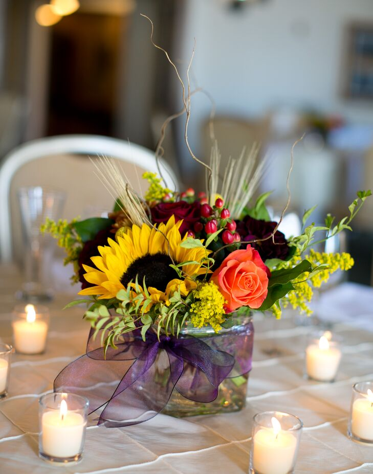 Matt and Paul wanted seasonal fall flower arrangements with a warm color palette. They went with a variety of red and orange flowers, including roses and berries for texture, as well as large sunflowers and lush greens.