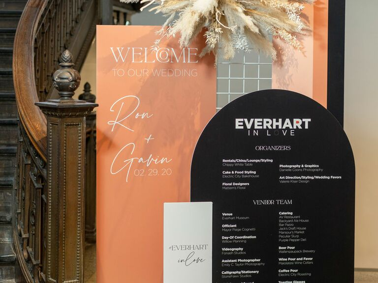Colorful wedding hashtag sign on seating chart at reception