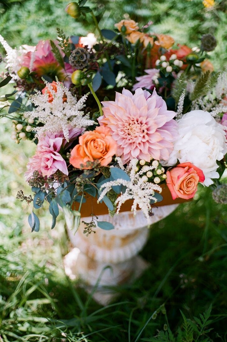 Stately stone urns were filled with a mix of dahlias, peonies, astilbe, roses and eucalyptus in shades of pink, coral, ivory and soft greens.