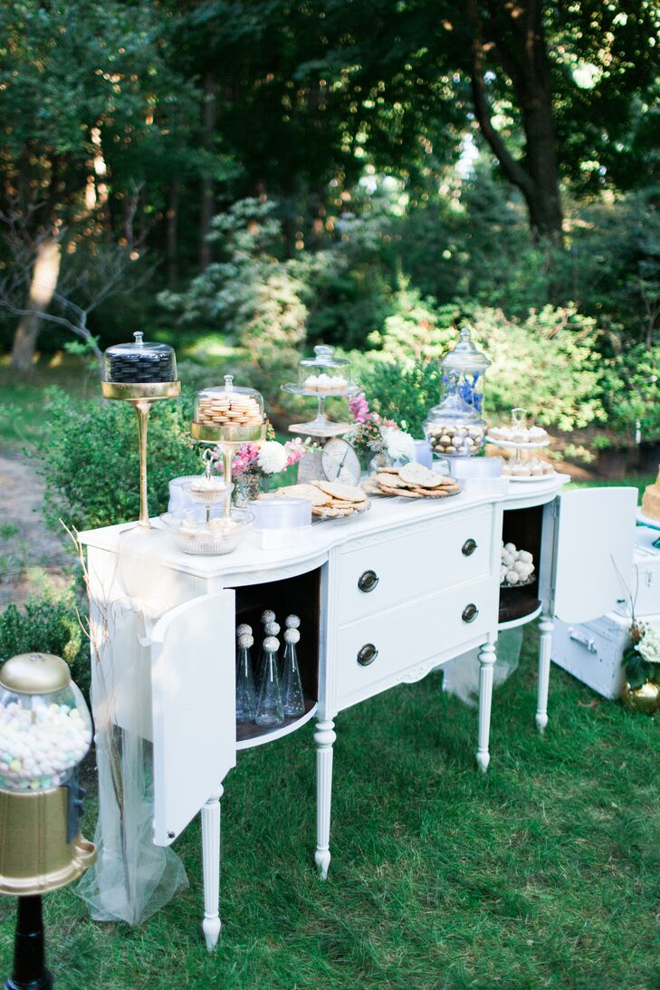 Delicious desserts were lined up on a vintage white antique buffet.