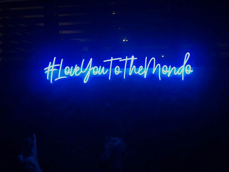 Neon blue wedding hashtag sign at reception