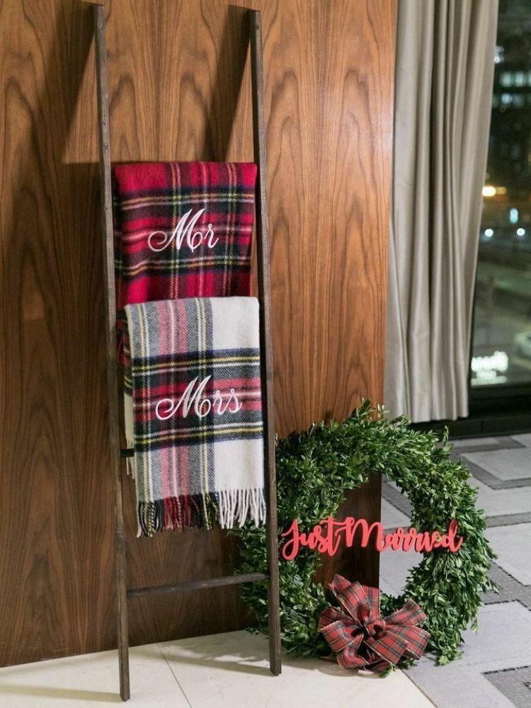 Custom plaid blankets hanging from ladder beside wreath