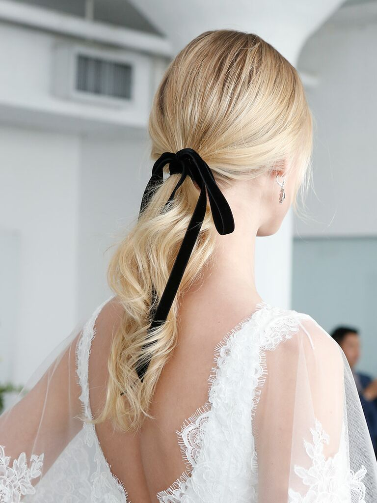 Low ponytail hairstyle with a black ribbon bow