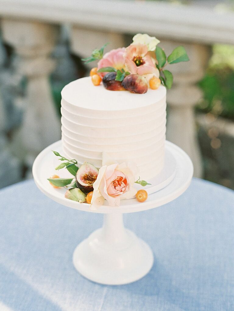 One-tier cake on white cake stand with fresh fruit and flower decorations