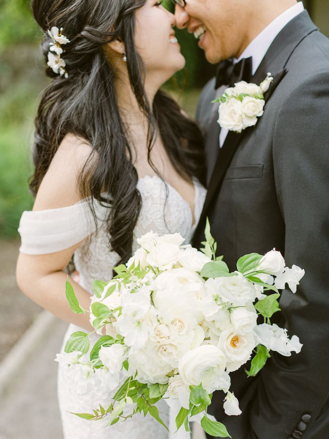 Bride and groom hugging while holding white bouquet