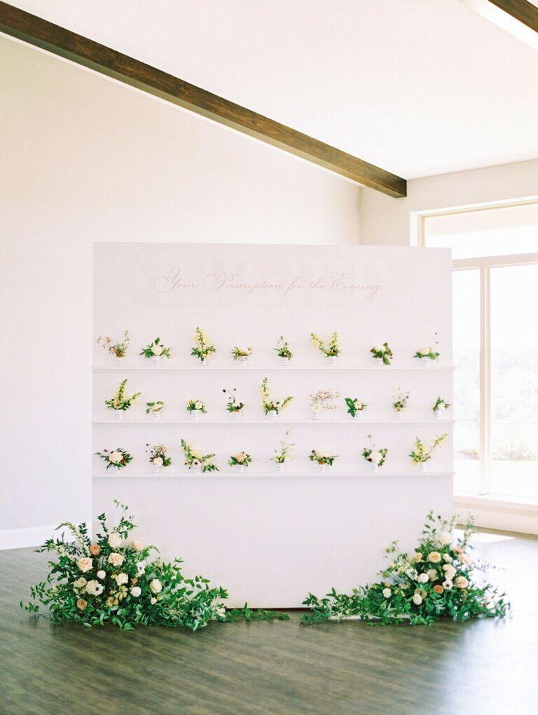 Pharmacy-inspired escort card display with mini flower arrangements