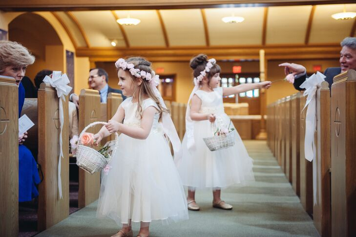 Flower girls wore classic sleeveless white dresses with tulle skirts and accessorized with ivory floral crowns. Each girl carried a basket of loose petals, befitting their roles.