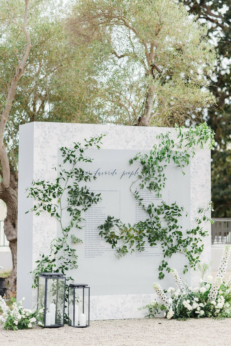 Large white seating chart display with greenery decorations
