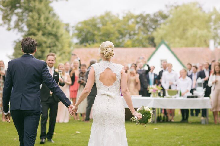 Ulrika wore a sheath ivory Maggie Sottero wedding dress with a deep V neckline and keyhole back. She loved the lace overlay that added a soft, romantic feel to her look. She completed the dress with a glamorous crystal belt for a little added sparkle.