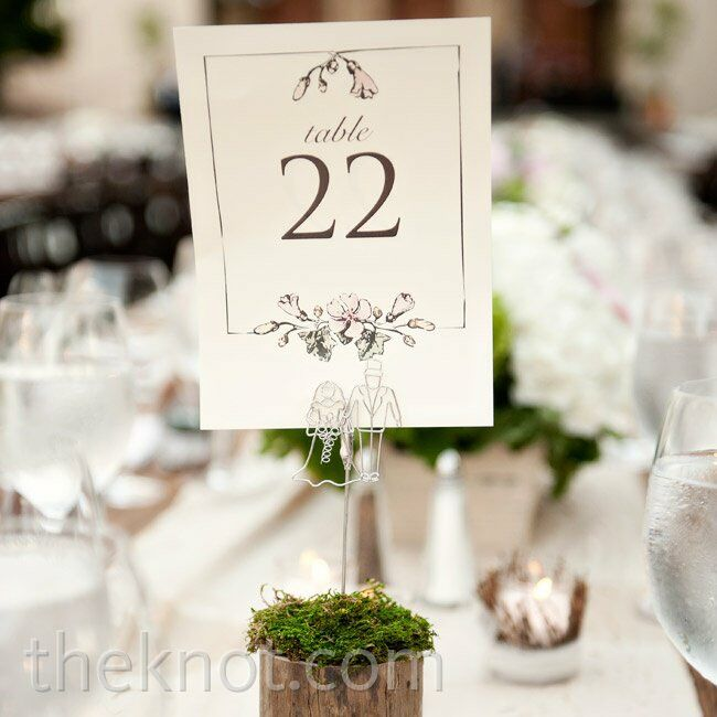 Simple table numbers were displayed on wooden rounds covered in moss.