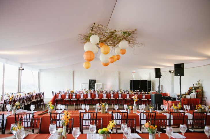 The reception was held in a large tent, where tables were topped with orange linens and a combination of driftwood and paper lanterns hung from the ceiling.